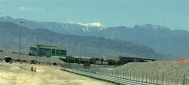 Driving west on 215 with the car thermometer reading 100 degrees you can still see snow in the Spring Mountains. (Jo Mitchell windshield photo)